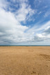 Sandy beach with blue sky at low tide at Benllech in Anglesey, North Wales