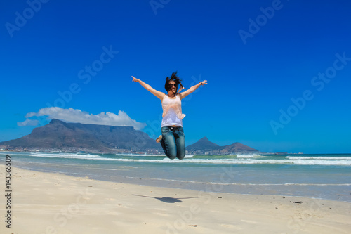 Fototapety, obrazy: Beautiful girl jumping at Milnerton beach, Cape Town. Table Mountain and breaking waves in the background. Concept photo of happiness, freedom and lifestyle.