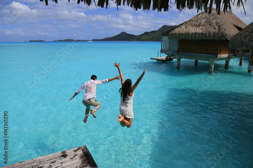 Fotografia  Happiness jump of young couple on the water