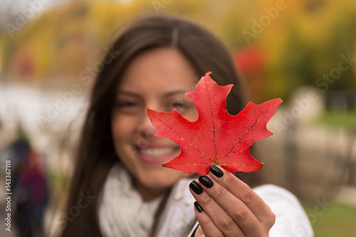 Poster Canada Beautiful smiling girl holding red maple leaf (Canada´s symbol) in a park in autumn, Focus at the red maple leaf, girl blurred.