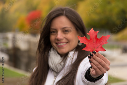 Spoed Foto op Canvas Canada Beautiful smiling girl holding red maple leaf (Canada´s symbol) in a park in autumn, Focus at the red maple leaf, girl blurred.