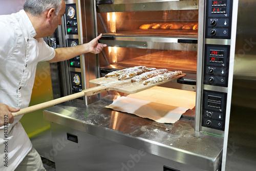 Fototapeta Baker bakes bread in oven obraz