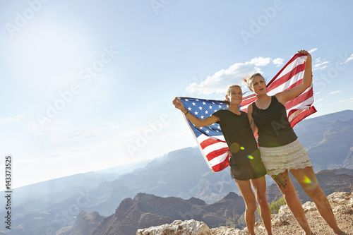 USA, Arizona, Young women embracing and holding US flag against Grand Canyon