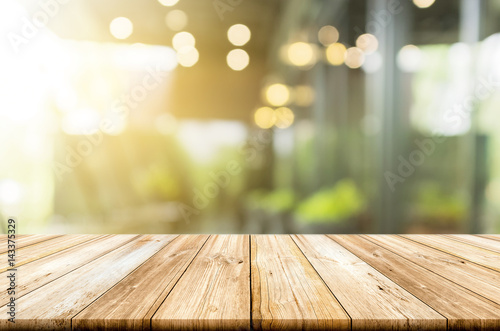 Fototapeta Empty light wood table top with blurred in coffee shop background obraz