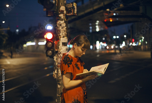 Germany, Berlin, Beautiful woman reading in city at night