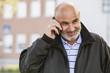 Sweden, Bleking, Solvesborg Bald man using cell phone