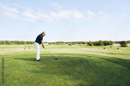 Senior man playing golf on a golf course