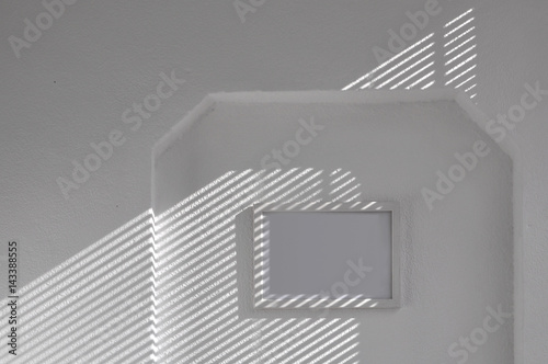 fototapeta na szkło Architectural background. White plastered wall with a diagonal shadow from the blinds and a white empty frame.