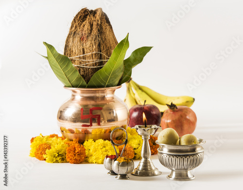 copper kalash with coconut and mango leaf with floral decoration, fruits, diya, sweet pedha,essential in hindu puja, front view, closeup