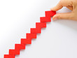 Concept of building success foundation. Women hand put red puzzle wooden blocks in the shape of a staircase