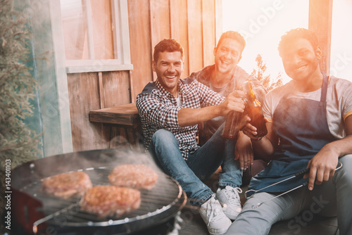 happy young friends making barbecue and drinking beer on porch with back light Fototapeta