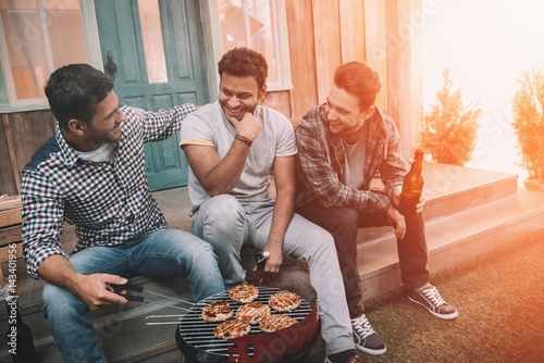 Fotografie, Obraz  Three young men drinking beer and smiling while sitting on porch and making barb