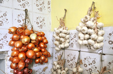 Bunches Of Garlic And Onion Are Dried On The Wall Of The Village Kitchen.