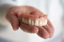 Closeup Of Womans Hand Holding A Teeth Denture