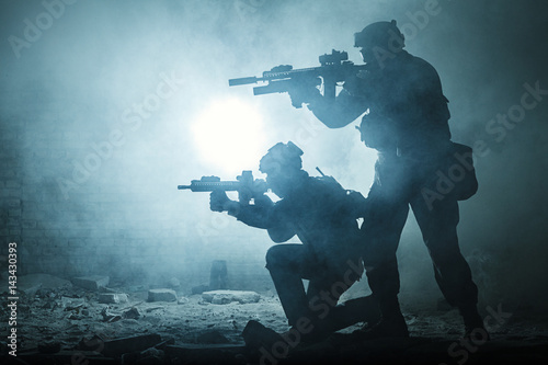 Black silhouettes of pair of soldiers in the smoke haze moving in battle operation Poster