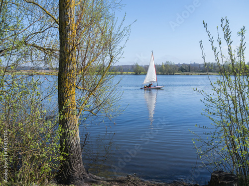 Staande foto Zeilen A sailing dinghy and its reflection on a peaceful blue lake, conningbrook lakes country park, with trees in the foreground.