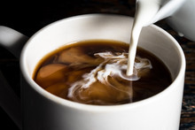Pouring Cream Into A Cup Of Co...