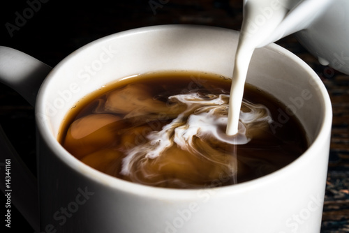 Photo  Pouring cream into a cup of coffee
