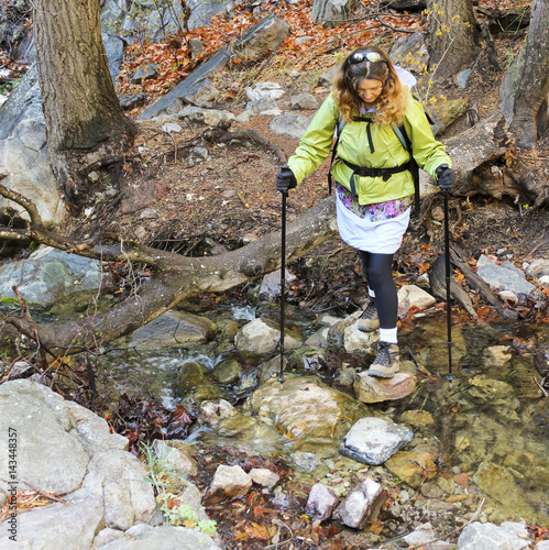 Photo  A Woman Hiker Crosses a Forest Creek