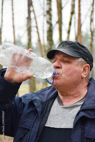 Mature caucasian man drinking water in the forest Canvas-taulu