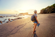Tropical Traveling. Young Woman With Camera And Backpack Walking Barefoot By Sea Beach Enjoying Sunset.