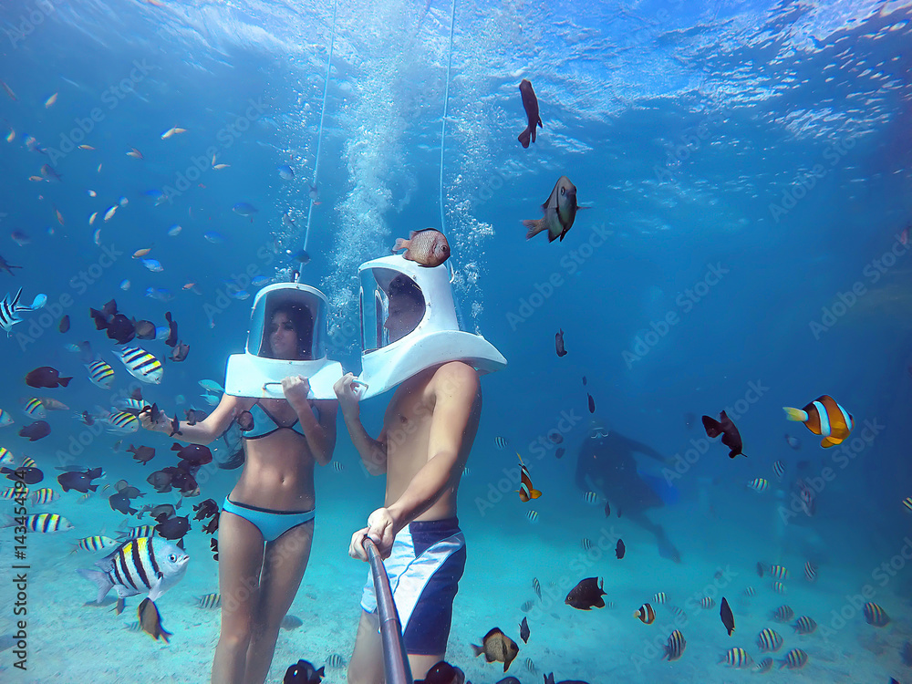Fototapeta Loving couple goes helmet diving together in tropical sea of Boracay during honeymoon and makes selfie on gopro