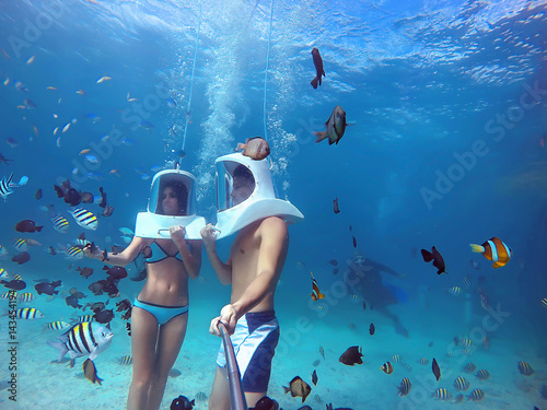 Fotografia Loving couple goes helmet diving together in tropical sea of Boracay during hone