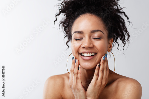 Foto  Portrait of happy female with her eyes closed touching a face against gray backg