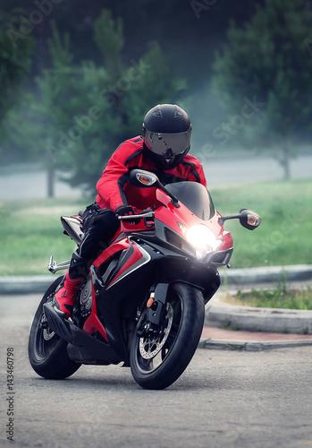 Biker in helmet ride on the red motorcycle Canvas Print