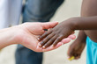 Caucasian woman's hand holding African little girl's hand outdoors