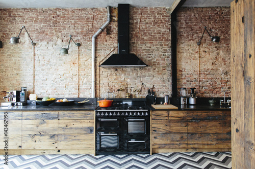Modern kitchen with exposed brick wall and lots of wood ...