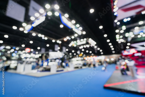 Obraz Blurred, defocused background of public event exhibition hall showing cars and automobiles, business commercial event concept - fototapety do salonu