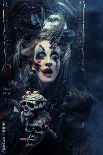 Ingelijste posters Halloween Young beautiful witch sits on a chair. Bright make up, skull, smoke- halloween theme.