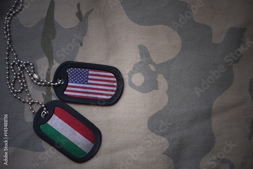 army blank, dog tag with flag of united states of america and hungary on the khaki texture background Tablou Canvas