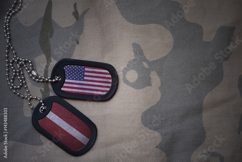Fotografie, Tablou  army blank, dog tag with flag of united states of america and latvia on the khaki texture background