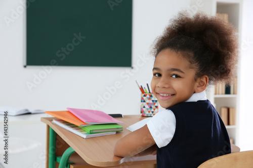 Fotografia Portrait of cute African-American girl in classroom