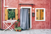Beautiful Colorful House Facade On Burano Island, North Italy. Red Wall With A Door And Two Windows With A Wooden Shutters, And A Dryer