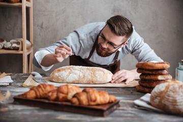 Koncentrirani muškarac pekar koji stoji u pekari blizu kruha.