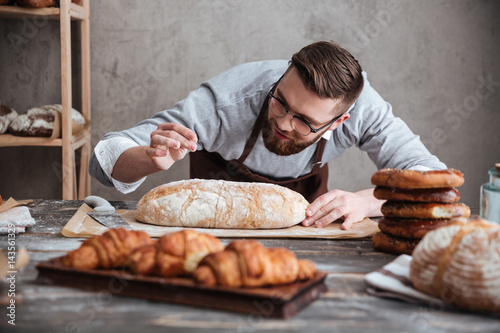 Concentrated man baker standing at bakery near bread.