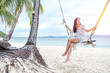 Beautiful woman sitting on a swing on the beach on Koh Phangan, Thailand