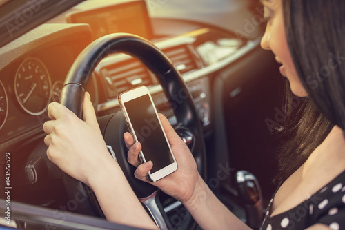 Valokuva  Woman looking at her smartphone while driving a car on a sunny day