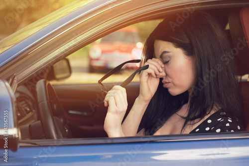 Woman having headache taking off glasses after driving car in traffic jam Canvas Print