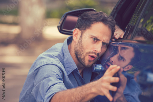 Fotografie, Obraz  Worried funny looking man obsessing about cleanliness of his new car