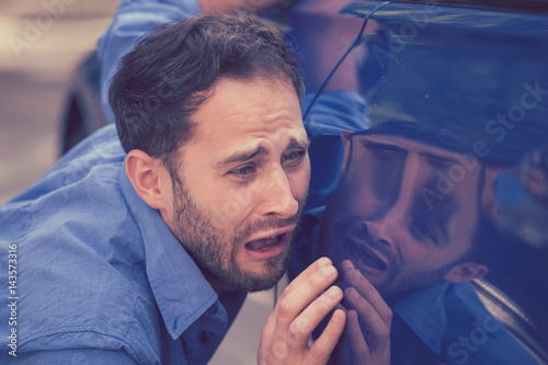 Fotografie, Obraz  Upset man looking at scratches and dents on his car outdoors