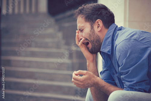 Obraz na płótnie sorrowful crying man sitting on steps outdoors