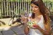 canvas print picture - junge frau ist in der stadt unterwegs und isst einen salat