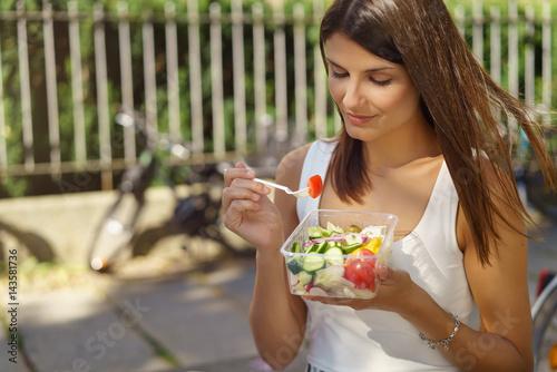 Fotografia  junge frau ist in der stadt unterwegs und isst einen salat