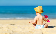 Baby Boy Sit Back With Toys  On Beach