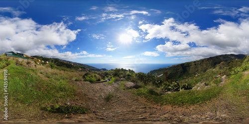 Spoed Foto op Canvas Grijze traf. Spherical panorama: View of the Atlantic Ocean on Madeira island next to the starting point of a levada trail. Blue sky and cumulus humilis clouds over the valleys of Tabua and Ponta do Sol.