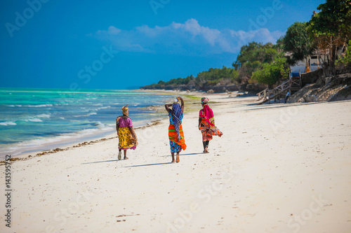 Spoed Fotobehang Zanzibar Three women walking on the beach in Jambiani, Zanzibar island, Tanzania